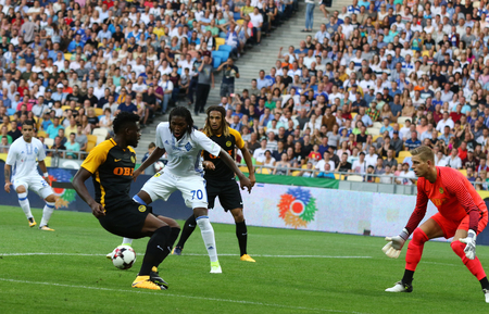 striker: KYIV, UKRAINE - JULY 26, 2017: Dieumerci Mbokani of FC Dynamo Kyiv (in White) scores a goal during UEFA Champions League 3rd qualifying round game against Young Boys at NSC Olimpiyskyi stadium in Kyiv Editorial