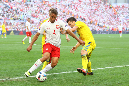 MARSEILLE, FRANCE - JUNE 21, 2016: Thiago Cionek of Poland (L) fights for a ball with Yevhen Konoplyanka of Ukraine during their UEFA EURO 2012 game at Stade Velodrome in Marseille, France