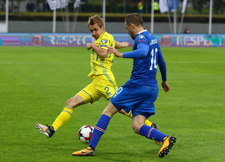 REYKJAVIK, ICELAND - SEPTEMBER 5, 2017: Gylfi Sigurdsson of Iceland (R) fights for a ball with Bohdan Butko of Ukraine during their FIFA World Cup 2018 qualifying game in Reykjavik, Iceland