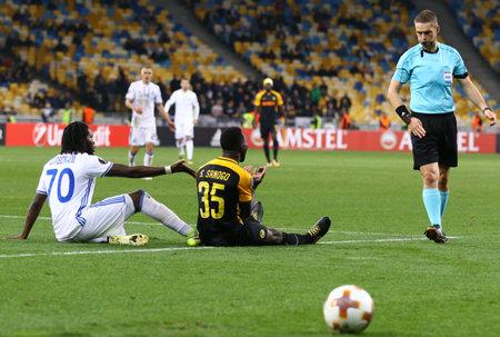 striker: KYIV, UKRAINE - OCTOBER 26, 2017: Dieumerci Mbokani of Dynamo Kyiv (L) and Sekou Sanogo of Young Boys seat on a grass during their UEFA Europa League game at NSC Olimpiyskyi stadium in Kyiv, Ukraine