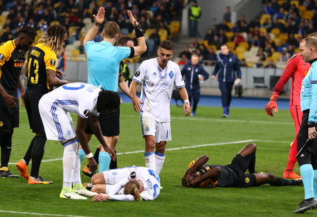 KYIV, UKRAINE - OCTOBER 26, 2017: Domagoj Vida of Dynamo Kyiv (in White) and Nicolas Moumi Ngamaleu of Young Boys lie on a grass after a head clash during their UEFA Europa League game