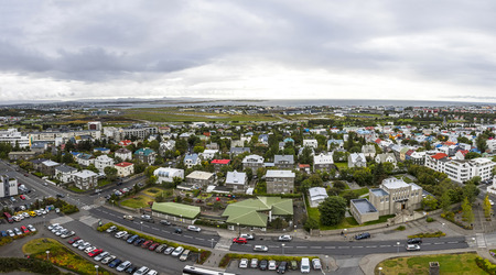 Picturesque panoramic aerial view of Reykjavik city, Iceland. Harbor, airport, skyline mountains and scenery beyond the city. View from the top of  Hallgrimskirkja Cathedral in center of Reykjavik