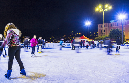 COMO, ITALY - DECEMBER 2, 2016: Ice skaters having fun on skating rink at annual traditional Christmas fair on Piazza Cavour in center of Como old town, Lombardy, Italy