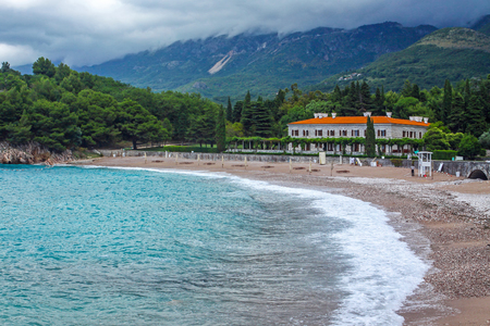 Picturesque summer view of Adriatic seacoast in Budva Riviera. Villa Milocer surrounded by the shady park. Milocer beach (Milocer plaza) on the foreground. Sveti Stefan, Montenegro