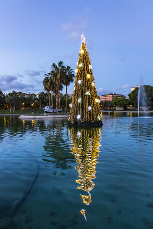 Close-up illuminated decorated New Year tree reflected in the water. Huelin Park, Malaga city, Andalusia, Spain Stock Photo