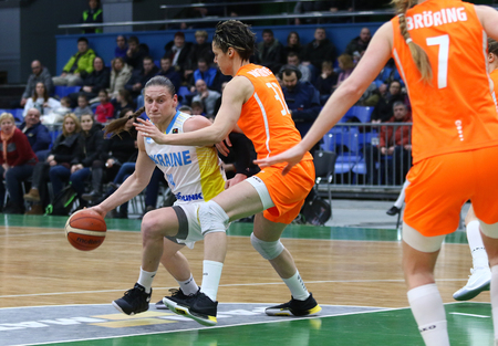 KYIV, UKRAINE - FEBRUARY 14, 2018: Alina Iagupova of Ukraine (L) fights for a ball with Dutch players during their FIBA Womens EuroBasket 2019 game at Palace of Sports in Kyiv. Ukraine won 84-49 Редакционное