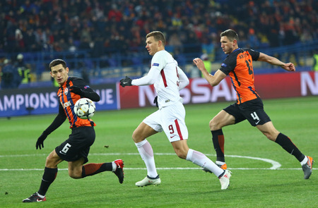 KHARKIV, UKRAINE - FEBRUARY 21, 2018: Taras Stepanenko (L) and Serhiy Kryvtsov (R) (both - Shakhtar) fight for a ball with Edin Dzeko of AS Roma during their UEFA Champions League Round of 16 game