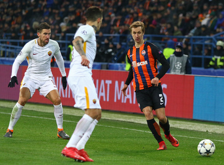 KHARKIV, UKRAINE - FEBRUARY 21, 2018: Bohdan Butko (R) of Shakhtar Donetsk fights for a ball with Kevin Strootman (L) and Diego Perotti of AS Roma during their UEFA Champions League Round of 16 game