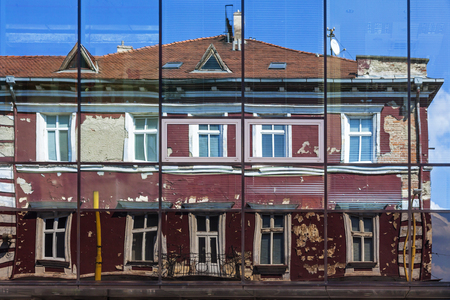 KOSICE, SLOVAKIA - AUGUST 29, 2015: Facade of an old building on Rooseveltova street reflected in the windows of modern DoubleTree by Hilton Hotel in Kosice downtown, Slovakia