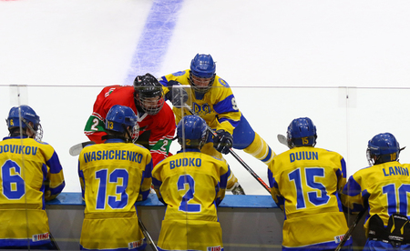 KYIV, UKRAINE - APRIL 17, 2018: Ukrainian players on bench looks on while L.KERESZTES of Hungary (L) fights for a puck with B.SEREDNITSKYY of Ukraine during the IIHF 2018 Ice Hockey U18 WC Div 1B game Editorial
