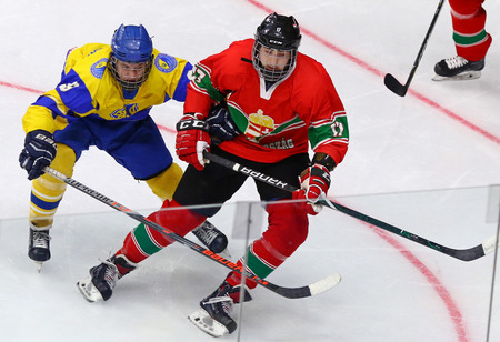 KYIV, UKRAINE - APRIL 17, 2018: Bohdan SEREDNITSKYY of Ukraine (L) fights for a puck with Marcell REVESZ of Hungary during their IIHF 2018 Ice Hockey U18 World Championship Div 1 Group B game Editorial