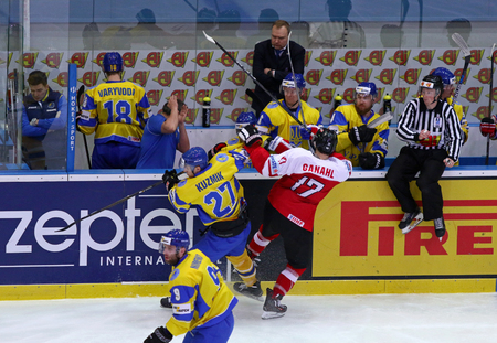 KYIV, UKRAINE - APRIL 25, 2017: Sergiy KUZMIK of Ukraine (#27) fights for a puck with Manuel GANAHL of Austria during their IIHF 2017 Ice Hockey World Championship Div 1A game at Palace of Sports Editorial