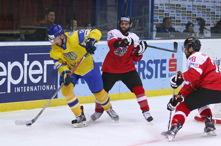 KYIV, UKRAINE - APRIL 25, 2017: Vladyslav GAVRYK of Ukraine (Yellow) fights for a puck with Austria players during their IIHF 2017 Ice Hockey World Championship Div 1A game at Palace of Sports in Kyiv Editorial