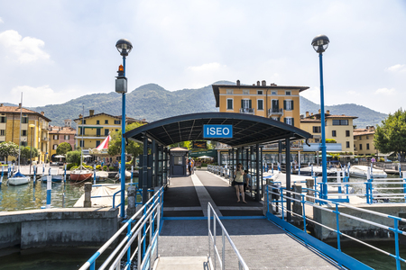 ISEO, ITALY - JUNE 17, 2017: Ferry station on Iseo lake (Lago dIseo) in Iseo city, Lombardy, Italy. View to the city from the pier. Iseo is a famous Italian resort