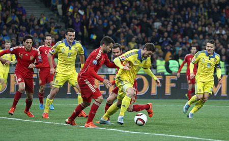 KYIV, UKRAINE - OCTOBER 12, 2015: Ukrainian (in yellow) and Spanish footballer players fight for the ball during their UEFA EURO 2016 Qualifying game at NSK Olimpiyskyi stadium in Kyiv. Spain won 1-0