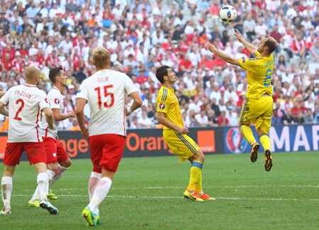 MARSEILLE, FRANCE - JUNE 21, 2016: Roman Zozulya of Ukraine (R) receives a ball during the UEFA EURO 2016 game against Poland at Stade Velodrome in Marseille, France. Poland won 1-0