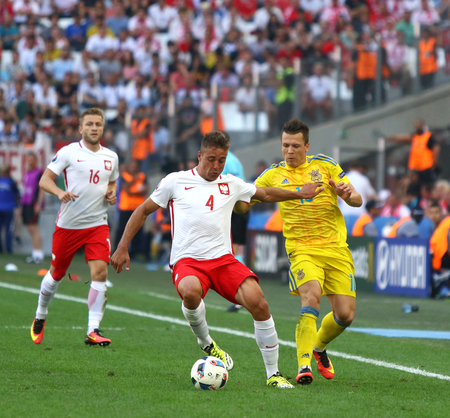 MARSEILLE, FRANCE - JUNE 21, 2016: Thiago Cionek of Poland (L) fights for a ball with Yevhen Konoplyanka of Ukraine during their UEFA EURO 2016 game at Stade Velodrome in Marseille, France