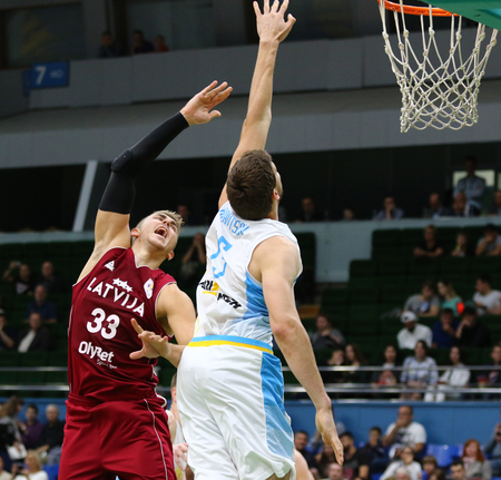 KYIV, UKRAINE - JULY 1, 2018: Martins Meiers of Latvia (L) and Viacheslav Kravtsov of Ukraine in action during their FIBA World Cup 2019 European Qualifiers game at Palace of Sports. Latvia won 93-71