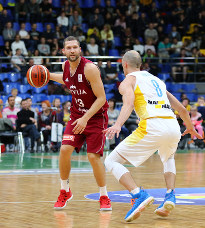 KYIV, UKRAINE - JULY 1, 2018: Janis Strelnieks of Latvia (L) and Sergii Gladyr of Ukraine in action during their FIBA World Cup 2019 European Qualifiers game at Palace of Sports. Latvia won 93-71 Редакционное