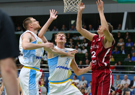 KYIV, UKRAINE - JULY 1, 2018: Igor Zaytsev (L), Artem Pustovyi (C) (both of Ukraine) and Arturs Ausejs of Latvia in action during their FIBA World Cup 2019 European Qualifiers game at Palace of Sports Editorial