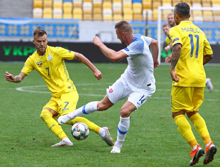 LVIV, UKRAINE - SEPTEMBER 9, 2018: Andriy Yarmolenko of Ukraine (L) fights for a ball with Milan Skriniar (C) of Slovakia during their UEFA Nations League game at Arena Lviv stadium. Ukraine won 1-0