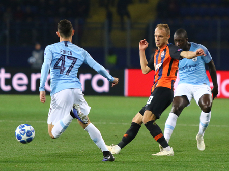 KHARKIV, UKRAINE - OCTOBER 23, 2018: Serhiy Bolbat of Shakhtar Donetsk (C) fights for a ball with Phil Foden of Manchester City (L) during their UEFA Champions League game at OSK Metalist stadium