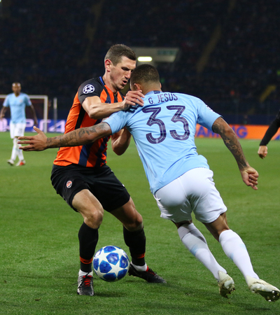 KHARKIV, UKRAINE - OCTOBER 23, 2018: Serhiy Kryvtsov of Shakhtar Donetsk (L) fights for a ball with Gabriel Jesus of Manchester City during their UEFA Champions League game at OSK Metalist stadium