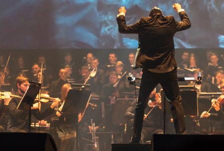 """Kiev, Oekraïne - 22 November 2018: Dirigent van Symphony Orchestra Andrey Chernyi presteert op het podium tijdens """"The Game of Thrones"""" concert in National Palace of Arts """"Oekraïne"""" in Kiev, Oekraïne Redactioneel"""