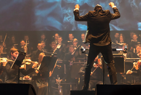 """KYIV, UKRAINE - NOVEMBER 22, 2018: Conductor of Symphony Orchestra Andrey Chernyi performs on stage during """"The Game of Thrones"""" concert at National Palace of Arts """"Ukraina"""" in Kyiv, Ukraine"""