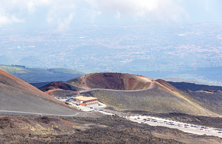 Crater Silvestri Inferiori (1886m) on Mount Etna, Etna national park, Sicily, Italy. Rifugio Sapienza - tourists parking and base station on the foothills of Mount Etna on the foreground Stock Photo