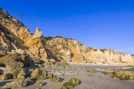 Praia do Porto de Mos, long beach in Lagos, Algarve region, Portugal. Beautiful golden beach, surrounded by impressive rock formations. Imagens