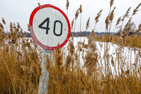 Old speed limit traffic sign on the side of the road Stock Photo