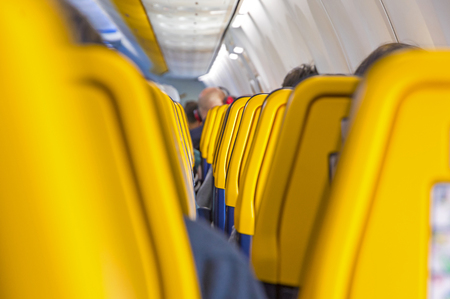 Las Palmas de Gran Canaria, Spain - December 13, 2018: Rows of yellow passenger seats inside the Boeing 737 aircraft, operated by Ryanair