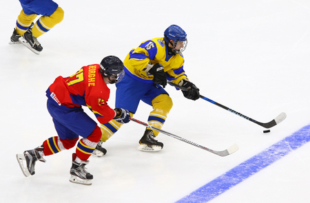 KYIV, UKRAINE - APRIL 20, 2018: Remus GHEORGHE of Romania (L) fights for a puck with Daniil DUIUN of Ukraine during their IIHF 2018 Ice Hockey U18 World Championship Div 1B game. Ukraine won 6-0 Editorial