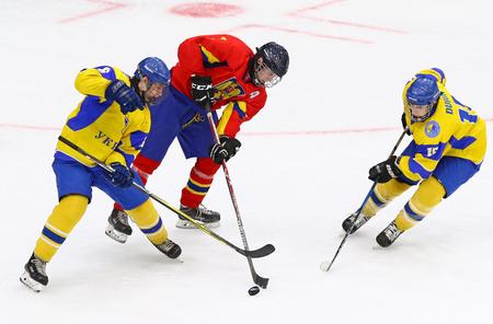 KYIV, UKRAINE - APRIL 20, 2018: Cristian BOLDIZSAR of Romania (C) fights for a puck with Stanislav SADOVIKOV (L) and Daniil DUIUN of Ukraine during their IIHF 2018 Ice Hockey U18 WC Div 1B game Editorial