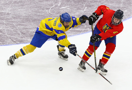 KYIV, UKRAINE - APRIL 20, 2018: Bogdan SEREDNITSKYY of Ukraine (L) fights for a puck with Zsolt SZABO of Romania during their IIHF 2018 Ice Hockey U18 World Championship Div 1B game. Ukraine won 6-0 Editorial