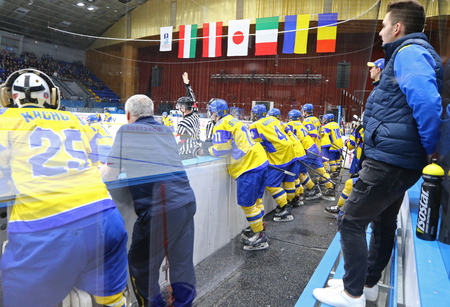 KYIV, UKRAINE - APRIL 20, 2018: Players of Ukraine National Team on a bench during the IIHF 2018 Ice Hockey U18 World Championship Div 1B game against Romania. Ukraine won 6-0