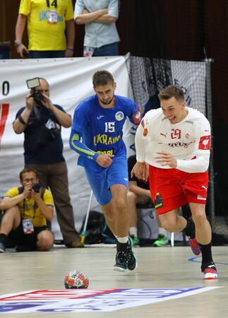 KYIV, UKRAINE - JUNE 12, 2019: Lasse Bredekjaer ANDERSSON of Denmark (R) fights for a ball with Oleksandr TILTE of Ukraine during their EHF EURO 2020 Qualifiers handball game at Palace of Sports