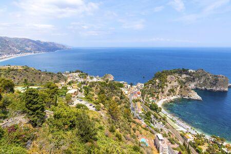 Aerial view of Giardini-Naxos bay and Ionian sea coast near Isola Bella island and Taormina town, Sicily, Italy