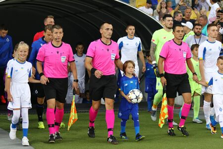 KYIV, UKRAINE - August 13, 2019: Referee Ivan Bebek, his assistants and players go to the pitch of NSC Olimpiyskyi stadium before the UEFA Champions League game FC Dynamo Kyiv v Club Brugge