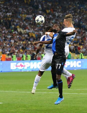 KYIV, UKRAINE - August 13, 2019: Clinton Mata of Club Brugge (C) fights for a ball with Gerson Rodrigues and Fran Sol of Dynamo Kyiv during their UEFA Champions League game at Olympic stadium in Kyiv Редакционное