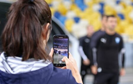 KYIV, UKRAINE - September 18, 2019: Journalist records a video on her smartphone while Malmoe players go to the pitch during the training session before UEFA Europa League game Dynamo Kyiv v Malmoe