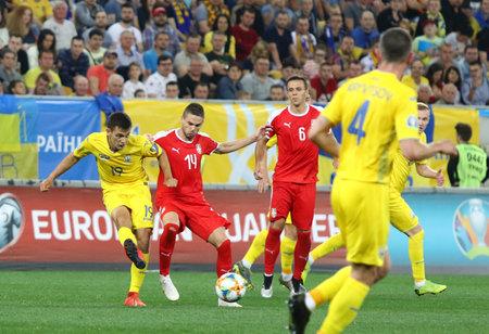 LVIV, UKRAINE - JUNE 7, 2019: Volodymyr Shepeliev of Ukraine (#19) fights for a ball with Mijat Gacinovic of Serbia (#14) during their UEFA EURO 2020 Qualifying game at Arena Lviv. Ukraine won 5-0 Редакционное