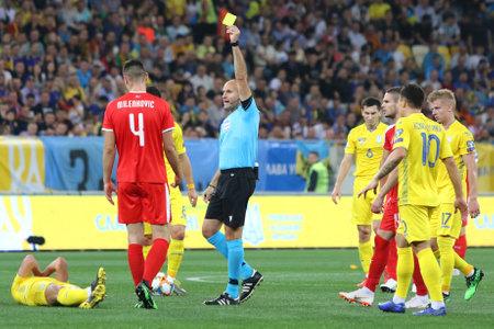 LVIV, Ucrania - 7 de junio de 2019: el árbitro Antonio Mateu Lahoz (ESP) muestra la tarjeta amarilla a Nikola Milenkovic de Serbia durante el partido de clasificación para la UEFA EURO 2020 Ucrania v Serbia en el estadio Arena Lviv Editorial