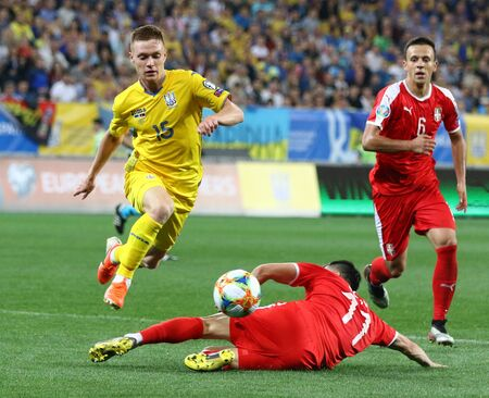 LVIV, UKRAINE - JUNE 7, 2019: Viktor Tsygankov of Ukraine (L) fights for a ball with Aleksandar Kolarov of Serbia during their UEFA EURO 2020 Qualifying game at Arena Lviv stadium. Ukraine won 5-0 Редакционное