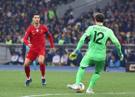 Kyiv, Ukraine - October 14, 2019: Cristiano Ronaldo of Portugal (L) and goalkeeper Andriy Pyatov of Ukraine in action during their UEFA EURO 2020 Qualifying game at NSK Olimpiyskyi stadium in Kyiv