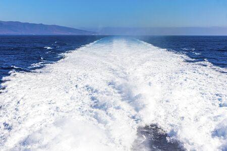 Water trail foaming behind a ferry boat in Atlantic ocean between Canary islands, Spain.