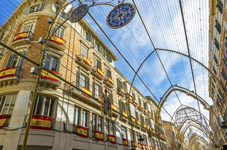 Buildings on Calle Marques de Larios street in the centre of Malaga city decorated with Spain flags and Christmas lights. Archivio Fotografico