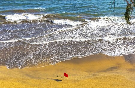 Red flag on the beach during the storm. Atlantic ocean coast, Las Palmas de Gran Canaria island, Canary islands, Spain