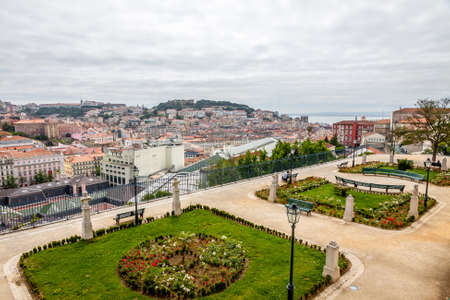 Panoramic aerial skyline view of Lisbon city, Portugal. View from Miradouro Sao Pedro de Alcantara viewpoint. Cloudy summer day